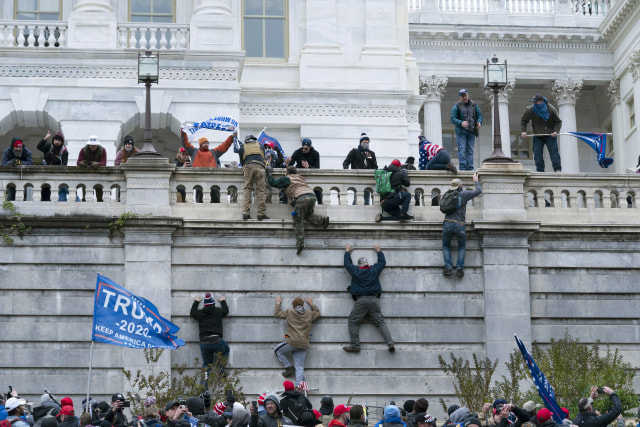FILE - In this Jan. 6, 2021 file photo rioting supporters of President Donald Trump climb the west wall of the U.S. Capitol in Washington. Historians say Trump's legacy and his electoral undoing will be largely shaped by rhetoric aimed at stirring his largely white base that tugged at the long-frayed strands of race relations in America. (AP Photo/Jose Luis Magana, File)