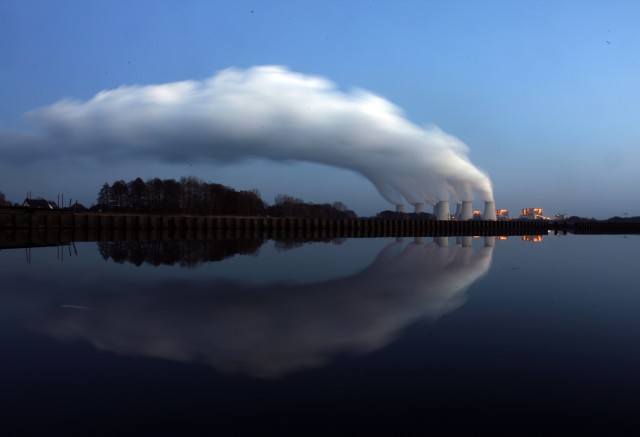 Steam billowing from the cooling towers of Vattenfall's Jaenschwalde brown coal power station is reflected in the water of a lake near Cottbus, eastern Germany December 2, 2009. Most world leaders plan to attend a climate summit in Copenhagen December 7-18, boosting chances that a new U.N. deal to fight climate change will be reached, host Denmark said on Tuesday. REUTERS/Pawel Kopczynski (GERMANY - Tags: ENVIRONMENT ENERGY)
