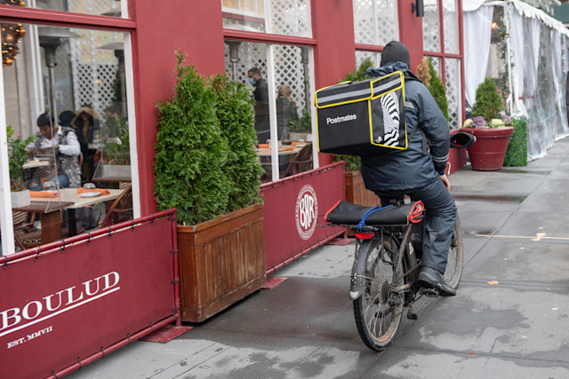 NEW YORK, NEW YORK - DECEMBER 25: A Postmates delivery driver rides past Epicerie Boulud on Christmas Day on December 25, 2020 in New York City. Many restaurants chose to stay open or work shorter hours on Christmas Eve and Christmas Day as a way to recoup profits as the pandemic continues to burden restaurants and bars struggling to thrive with evolving government restrictions. (Photo by Alexi Rosenfeld/Getty Images)