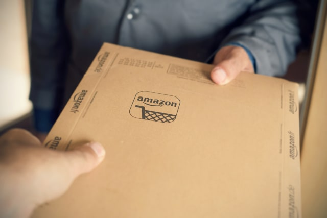 Barcelona, Spain - November 2, 2017: A courier delivers an Amazon package to a costumer. Amazon is an important worldwide online shopping company based in the United States