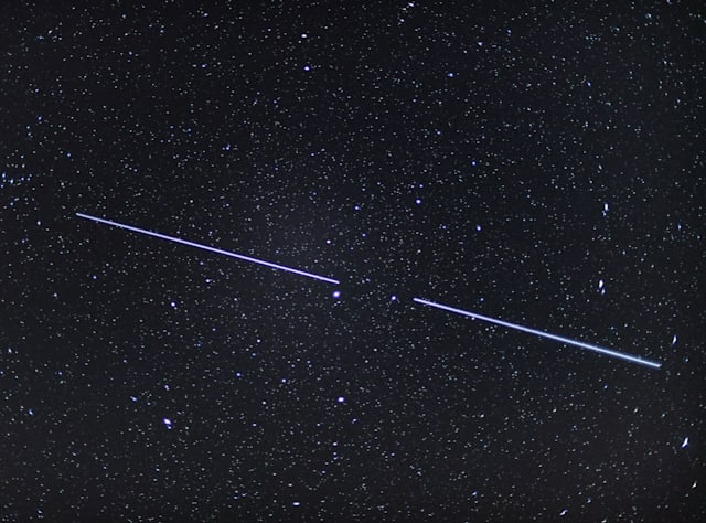 """18 April 2020, Brandenburg, Sieversdorf: Two """"Starlink"""" satellites can be seen as stripes of light in the night sky (shot with an exposure time of 15 seconds). In early January 2020, 60 satellites were launched into space for the third time for the Starlink project. Starlink is a project of Elon Musk and his SpaceX company. Since May 2019, 180 such communication satellites have been launched into orbit. Photo: Patrick Pleul/dpa-Zentralbild/dpa (Photo by Patrick Pleul/picture alliance via Getty Images)"""