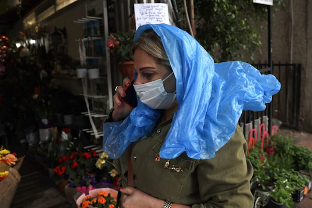 An Israeli woman, wearing protective mask amid the COVID-19 pandemic, speaks on the phone as she walks past a shop in the central Israeli city of Ramat Gan on May 5, 2020. - Israel cancels restrictions preventing people to walks up to 100 meter and also prepare to reopen markets and shopping malls on the coming days. (Photo by MENAHEM KAHANA / AFP) (Photo by MENAHEM KAHANA/AFP via Getty Images)