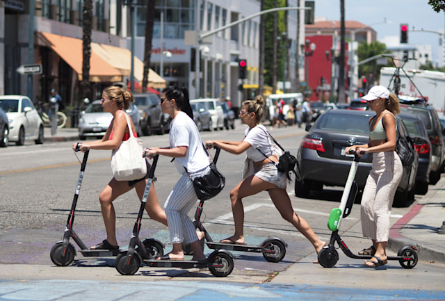 Young women ride shared electric scooters in Santa Monica, California, on July 13, 2018. - Cities across the U.S. are grappling with the growing trend of electric scooters which users can unlock with a smartphone app. Scooter startups including Bird and Lime allow riders to park them anywhere that doesn't block pedestrian walkways but residents in some cities, including Los Angeles, say they often litter sidewalks and can pose a danger to pedestrians. (Photo by Robyn Beck / AFP)        (Photo credit should read ROBYN BECK/AFP via Getty Images)