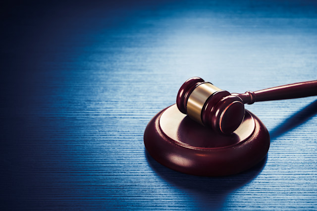 high contrast image of Judge gavel on a blue wooden background