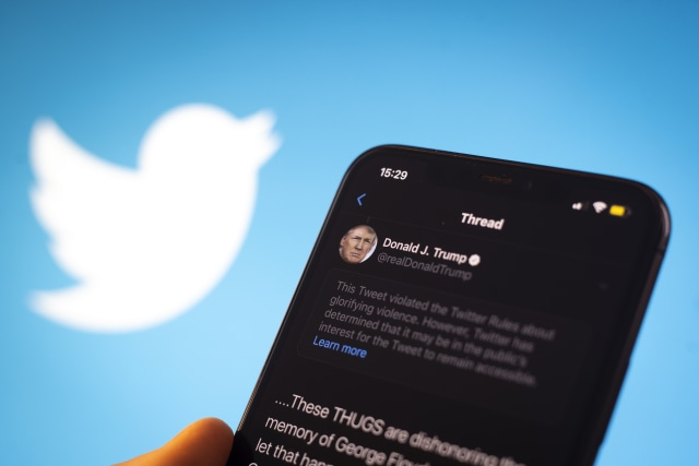 A tweet by US president Donald Trump is seen being flagged as inciting violence by Twitter in this photo illustration on an Apple iPhone in Warsaw, Poland on May 29, 2020. Twitter on May 29 applied a fact-checking label to a vote-in-mail tweet by US President Donald Trump that the company considers misleading. Twitter has recently started labelling tweets with public notification and fact check labels. The labelling of Trump's tweet about the uproar following the death of George Floyd has seen the president signing an executive order targeting the Communications Decency Act. Section 230 which protects social media companies against lawsuits against them for user generated content. (Photo Illustration by Jaap Arriens/NurPhoto via Getty Images)