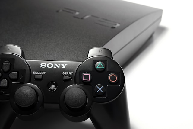 Indianapolis, Indiana, USA - March 23rd, 2011: A 120GB slim version of Sony's Playstation 3 sits isolated on white with one of the system's wireless controllers placed up against the console.
