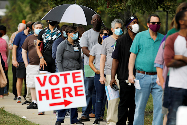Voters wait in line to enter a polling place and cast their ballots on the first day of the state's in-person early voting for the general elections in Durham, North Carolina, U.S. October 15, 2020.    REUTERS/Jonathan Drake     TPX IMAGES OF THE DAY