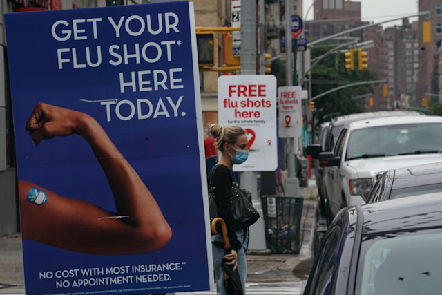 A woman walks past free flu shot advertisements outside of drugstores on August 19, 2020 in New York. (Photo by Bryan R. Smith / AFP) (Photo by BRYAN R. SMITH/AFP via Getty Images)