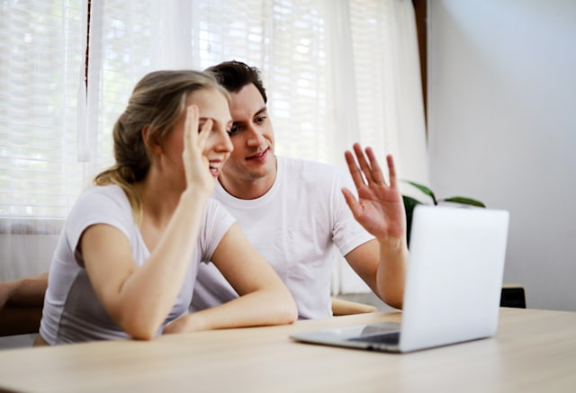 Happy couple lover talking and waving hand in a video conference on line with a laptop for contact friendship at home.