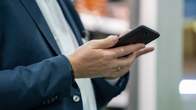 Businessman With Smartphone At Trade Fair