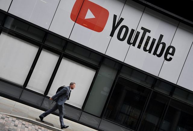 A worker walks past YouTube offices, in King's Cross, London, Britain, September 11, 2020. REUTERS/Toby Melville