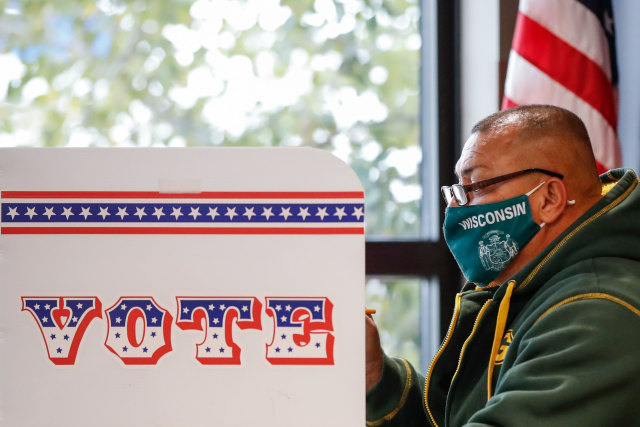 A man casts his ballot at Tippecanoe Library on the first day of in-person early voting for the November 3rd elections in Milwaukee, Wisconsin, on October 20, 2020. - Early voting kicked off October 20, 2020 in Wisconsin, a state fought over by President Donald Trump and Democratic challenger Joe Biden as their contentious White House race enters its final 14-day stretch. (Photo by KAMIL KRZACZYNSKI / AFP) (Photo by KAMIL KRZACZYNSKI/AFP via Getty Images)