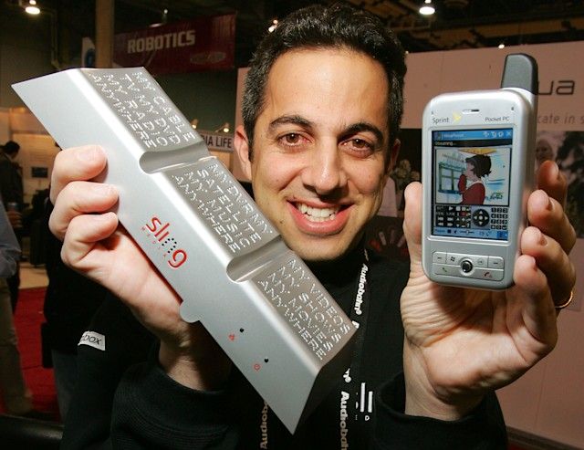 LAS VEGAS - JANUARY 06:  Sling Media co-founder Jason Krikorian displays the Slingbox (L) and a Sprint mobile device with SlingPlayer Mobile software playing a streaming image off his television set from his home at the International Consumer Electronics Show January 6, 2006 in Las Vegas, Nevada. The Slingbox plugs into a customer's DVR or cable box and with the new software, users can access their home television on any Windows phone or laptop anywhere in the world. The 1.6 million square-foot consumer electronics show, which runs through January 8, is expected to draw over 120,000 attendees.  (Photo by Ethan Miller/Getty Images)