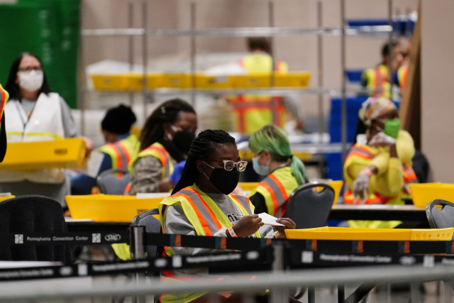 A Philadelphia election workers processes mail-in and absentee ballots for the general election at the Pennsylvania Convention Center, Tuesday, Nov. 3, 2020, in Philadelphia. (AP Photo/Matt Slocum)
