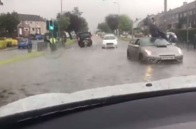 Man left sitting on car roof as streets flood after heavy rain