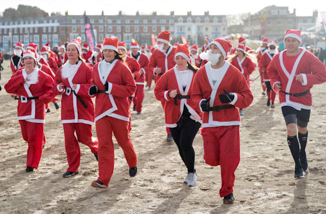 In pictures: Pudding pursuit sees Santas take to beach