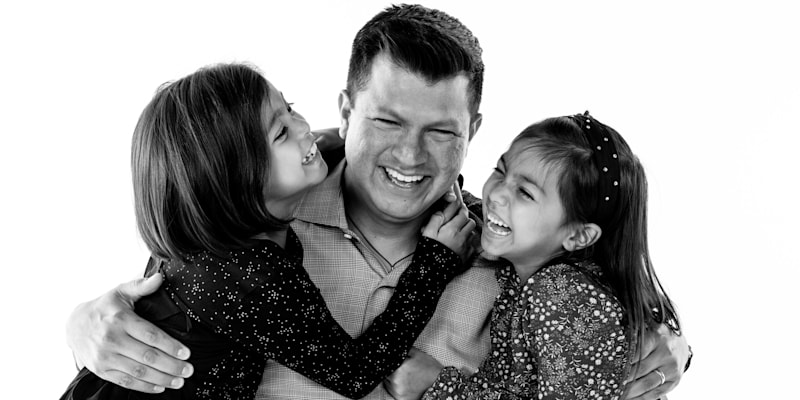 A father and two children embrace and laugh together.