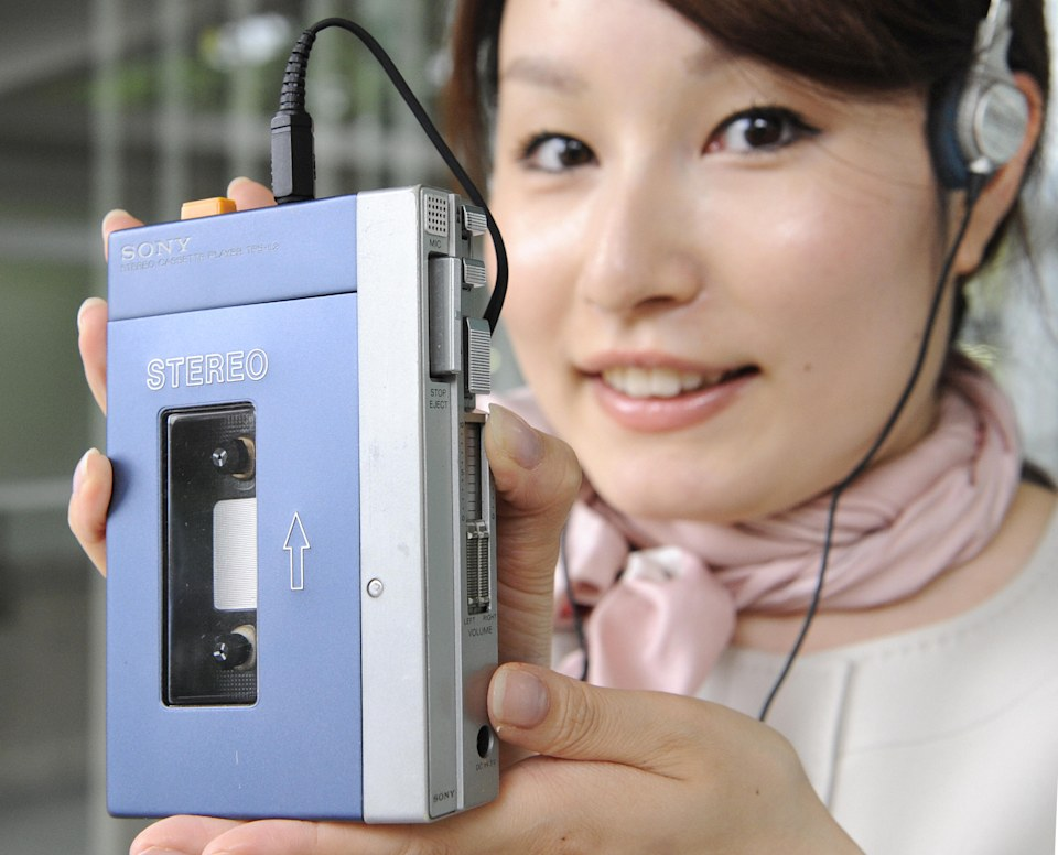 """Japan's electronics giant Sony employee dispays the first model of Sony's stereo cassete player """"Walkman TPS-L2"""" at the company's museum in Tokyo on July 1, 2009.  Thirty years ago Sony launched the Walkman, a gadget which revolutionised the way people around the world listened to music but has since been overtaken by an icon of the digital age.  Sony sold 30,000 Walkmans in the first two months after its launch, and 50 million within a decade.   AFP PHOTO / Yoshikazu TSUNO (Photo credit should read YOSHIKAZU TSUNO/AFP/Getty Images)"""
