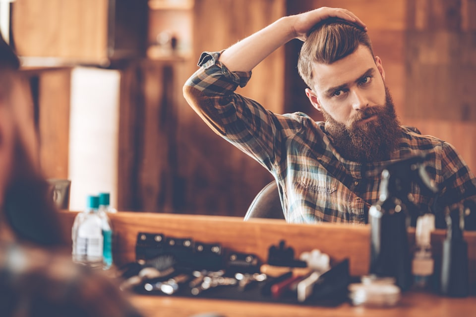 Handsome young bearded man looking at his reflection in the mirror and keeping hand in hair while sitting in chair at barbershop