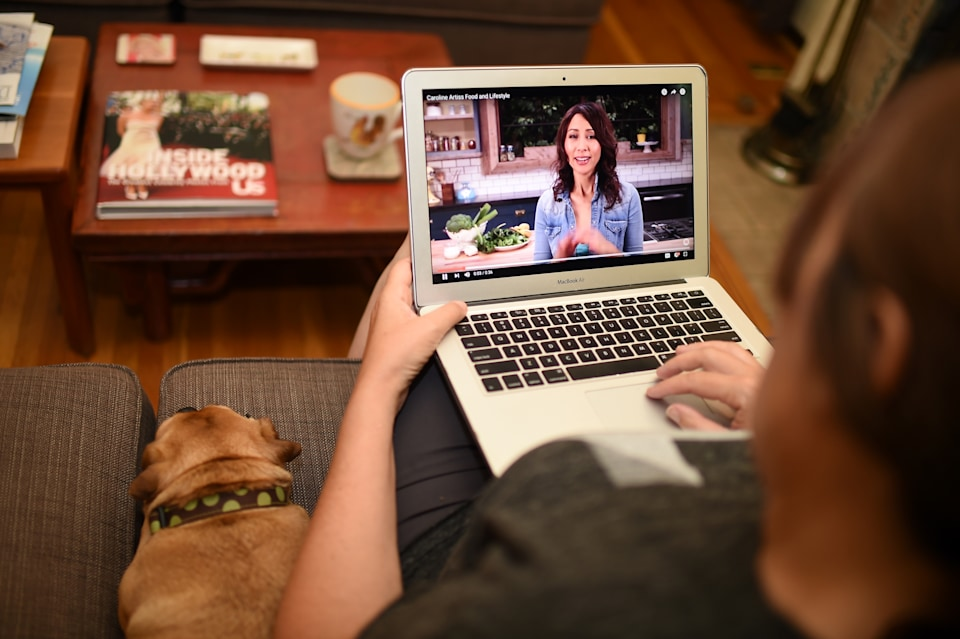 In this photo illustration, a woman and a dog watch a video by chef and YouTuber Caroline Artiss on her YouTube page, July 2, 2016 in Los Angeles, California. Self-described YouTuber Caroline Artiss has been a chef for 20 years, but opted out of restaurants and went to work for herself in catering in 2008. Then, a friend showed her how simple it was to make videos for YouTube. A media revolution is taking place, and most people over 35 years of age aren't tuned in. Millennials and their successors are shunning old-school television in favor of watching what they want whenever they wish on Google-owned YouTube or other video platforms like Dailymotion or Facebook.  / AFP / Robyn Beck        (Photo credit should read ROBYN BECK/AFP via Getty Images)