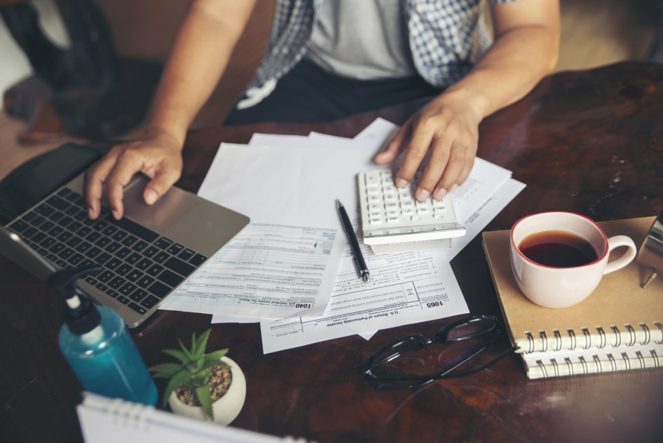 Budget planning concept, Accountant calculating tax and using mobile phone,  work online at home. Calendar 2019 and personal annual tax forms for individual income under US law placed on office desk.