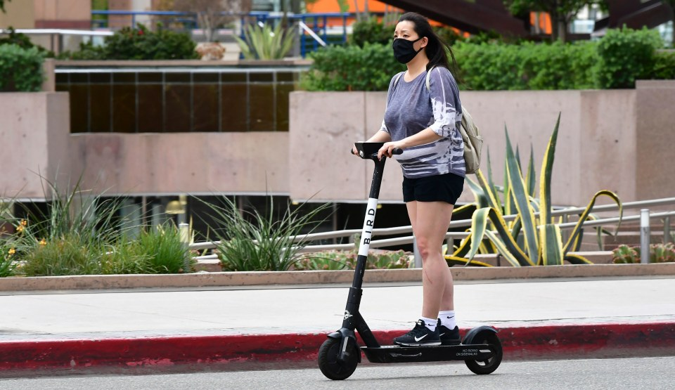 "A commuter on electric scooter wears her facemask  in Los Angeles on June 29, 2020 where the largest single-day number of new COVID-19 cases in the county since the pandemic began was confirmed, with a spike among the younger population. - The coronavirus pandemic is ""not even close to being over"", the WHO warned today, as the global death toll passed half a million and cases surge in Latin America and the United States. (Photo by Frederic J. BROWN / AFP) (Photo by FREDERIC J. BROWN/AFP via Getty Images)"