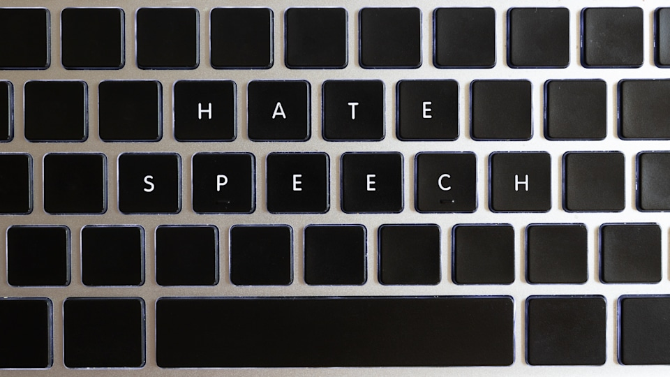 Concept of problems of today internet. Hate speech caption isolated on notebook keyboard with blank keys.