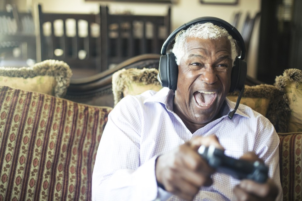 A senior black man having fun playing video games  with a headset to communicate with his team