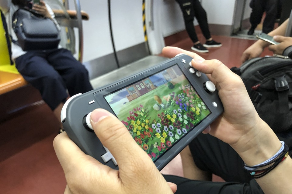 BEIJING, CHINA - JUNE 14: A passenger uses a Nintendo Switch to play video game 'Animal Crossing: New Horizons' on a subway train of Beijing Subway Line 1 on June 14, 2020 in Beijing, China. (Photo by VCG/VCG via Getty Images)