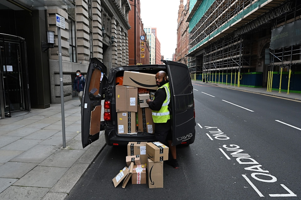 A delivery driver unloads Amazon-branded boxes in Manchester, northwest England as the country battles a surge in coronavirus cases on October 19, 2020 (Photo by Paul ELLIS / AFP) (Photo by PAUL ELLIS/AFP via Getty Images)