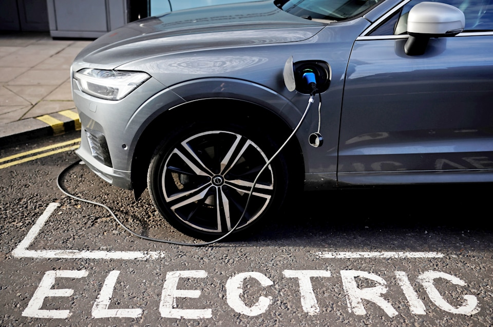 """An EV charging next to the word """"electric"""" painted on the pavement."""