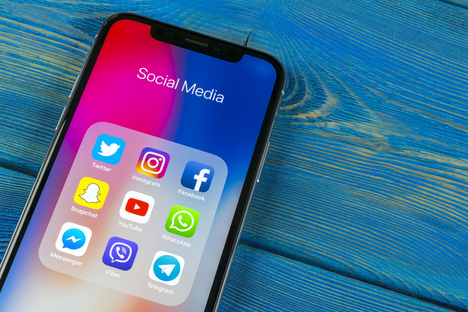Apple iPhone X on office desk with icons of social media facebook, instagram, twitter, snapchat application on screen. Social network. Starting social media app.