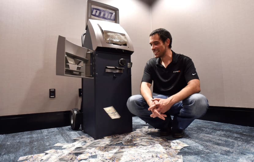 Weston Hecker, senior security engineer at Rapid 7 smiles as he watches phony money dispense automatically from an ATM after it was hacked during a demonstration at the 2016 Black Hat cyber-security conference in Las Vegas, Nevada, U.S. August 3, 2016.  REUTERS/David Becker