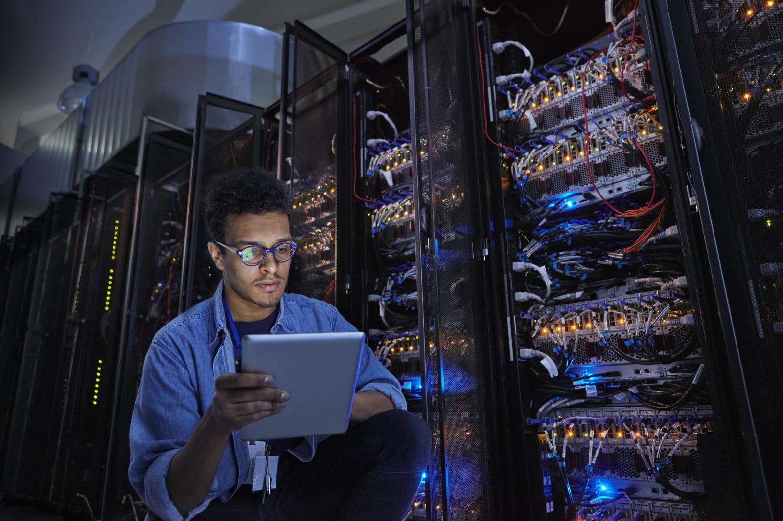 Focused male IT technician using digital tablet in dark server room