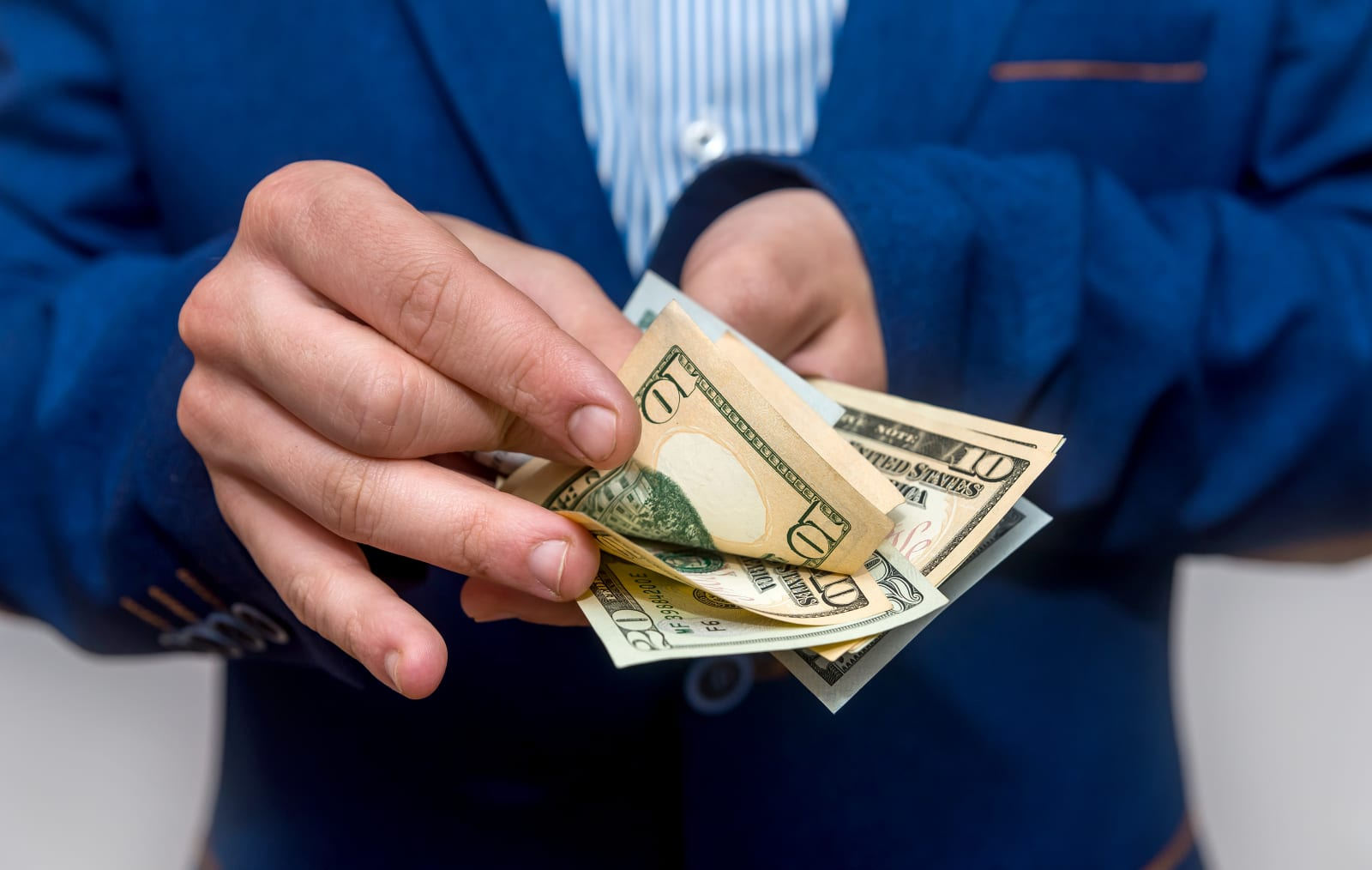 Male hands counting dollar banknotes close up