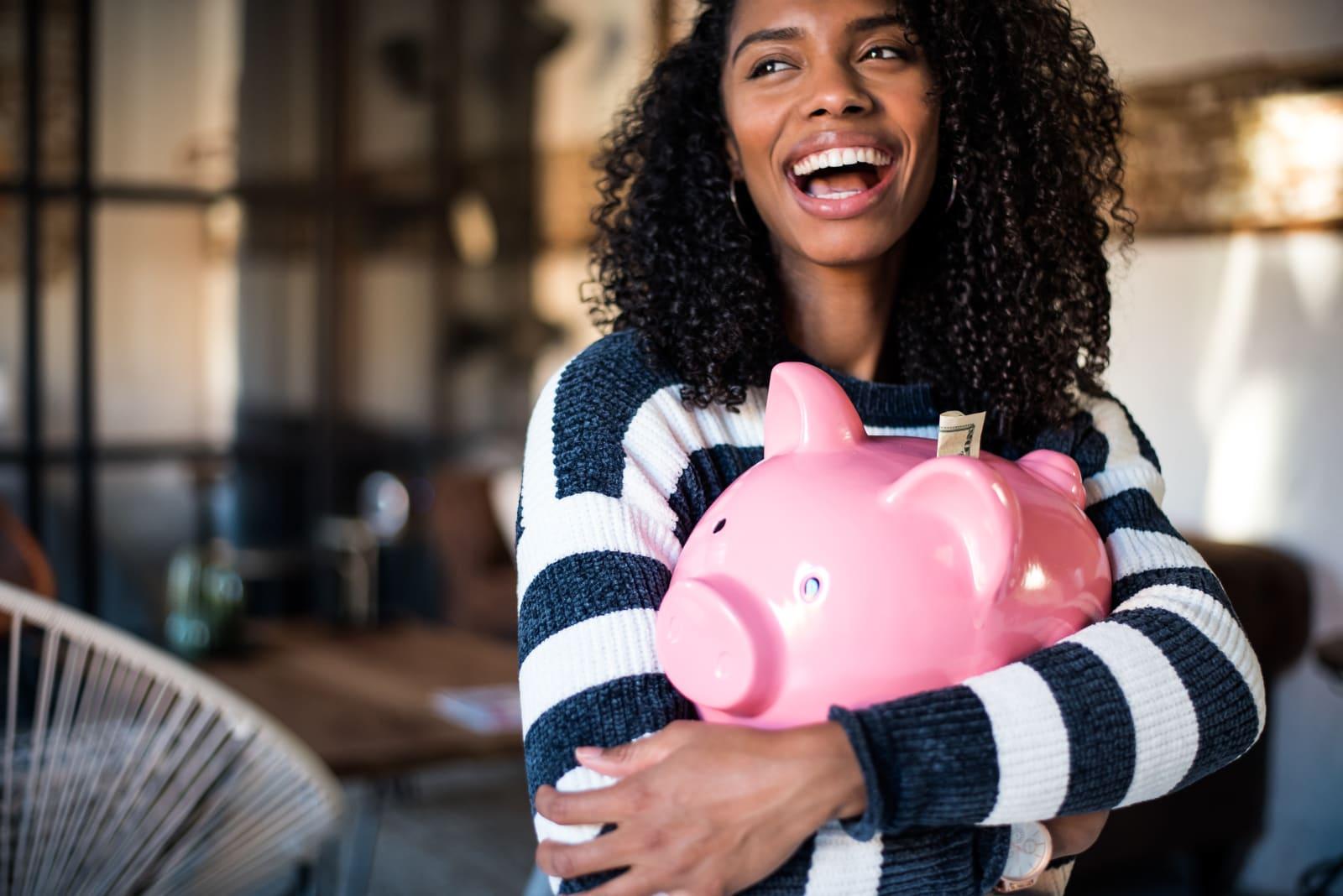 Black woman hugging her piggy bank