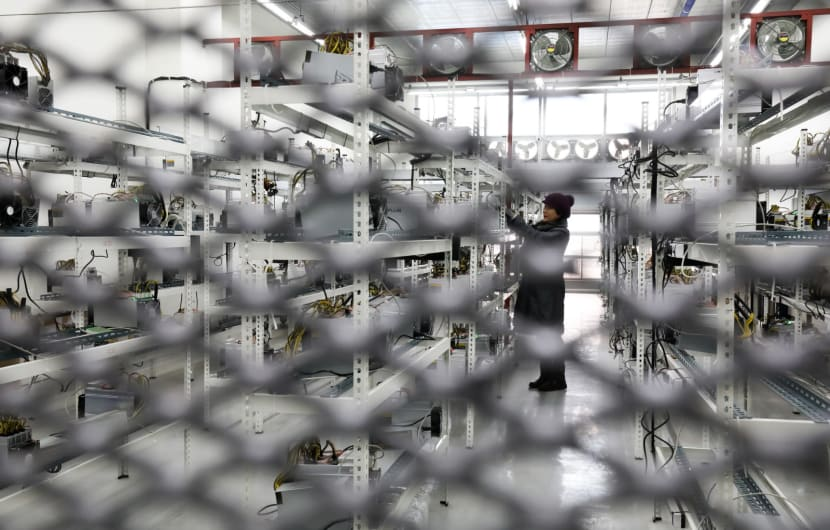 Seo Hee-jin is seen behind a barrier as she inspects application-specific integrated circuit (ASIC) devices and power units, manufactured by Bitmain Technologies Inc., at her cryptocurrency mining facility in Incheon, South Korea, on Friday, Dec. 15, 2017. Hedge funds are pulling out of gold bets as more exciting moves in equities and cryptocurrencies make safe-haven investments look boring. Photographer: SeongJoon Cho/Bloomberg via Getty Images